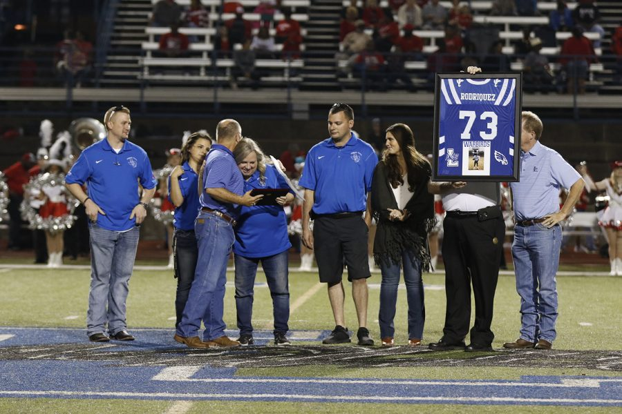 The Rodriquez family receives a plaque from the athletic department, as well as a framed jersey in honor of the late Jesse Rodriquez.