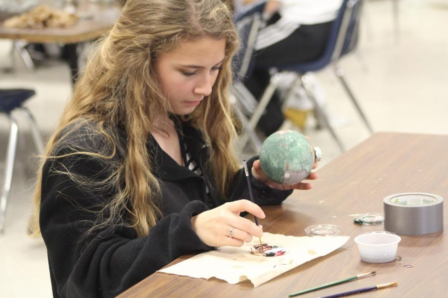 Senior Chloe Bryant paints the Pickers Pavilion on the ornament. It will be displayed on the House of Representatives Christmas tree.