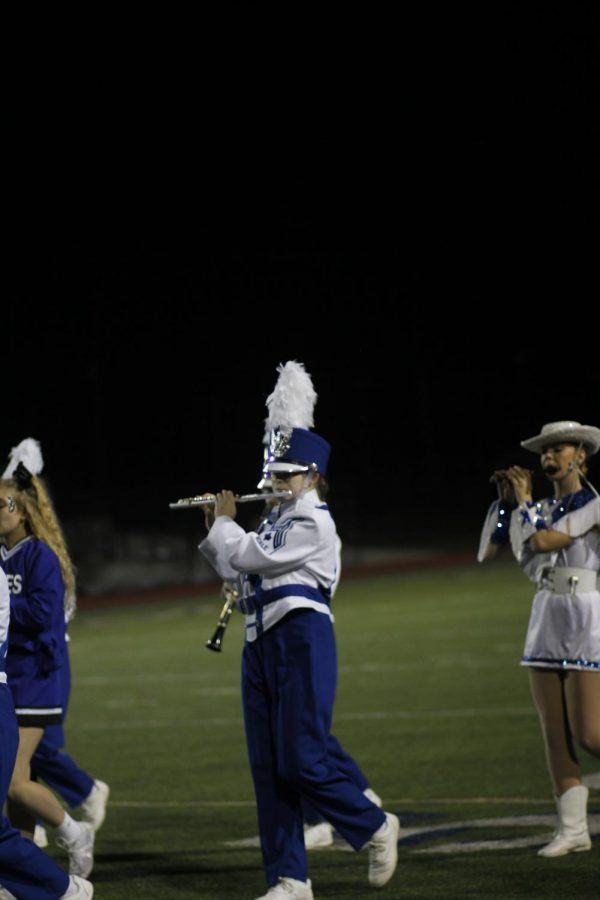 Sophomore Elizabeth Stone plays her flute as she marches down the field. The band performed the drill they march at contest.