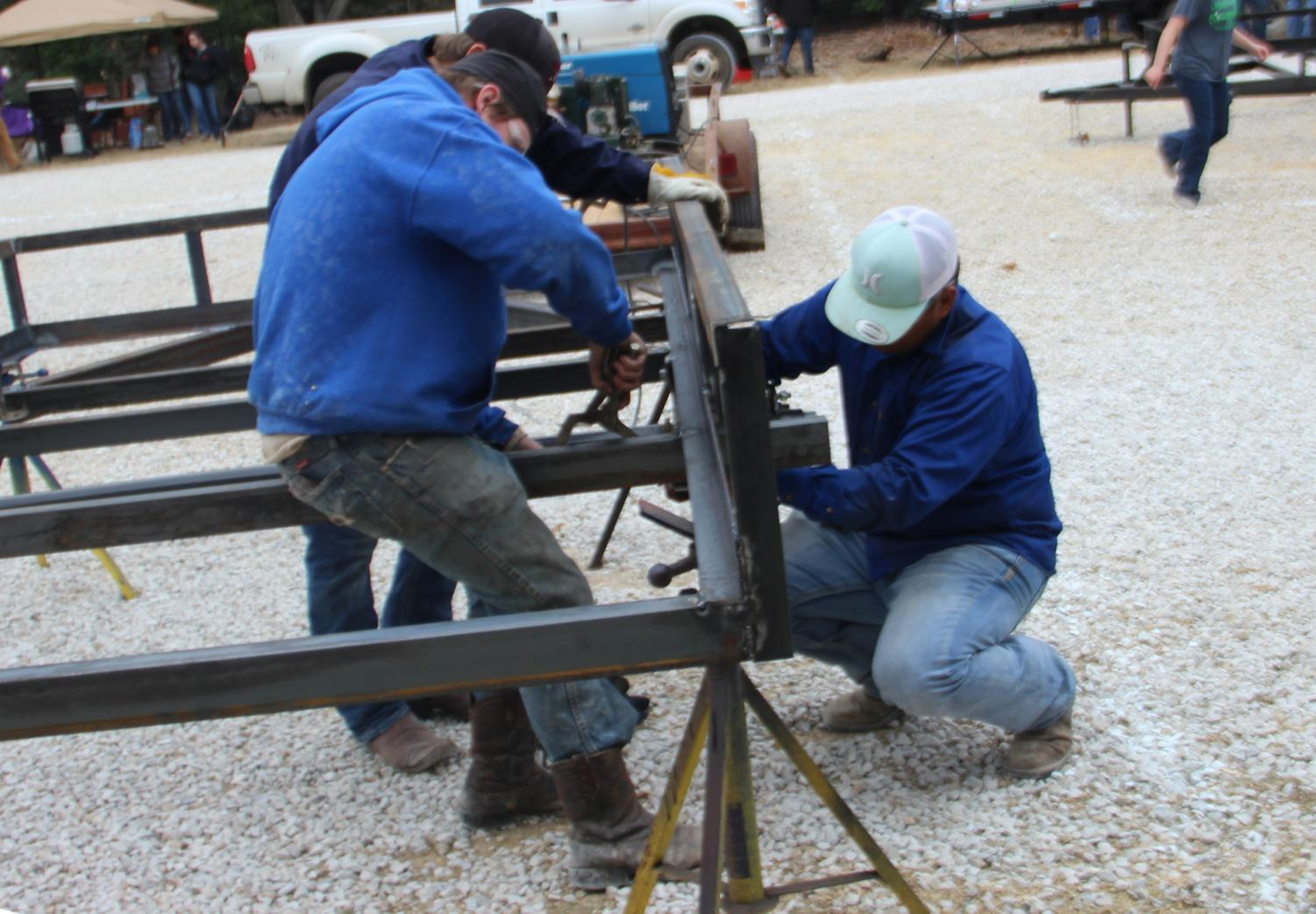 Three Lindale students work on their trailer at the trailer build on December 6. Several Lindale teams competed in either the trailer build off or the cooking competition, along with teams from different schools around the area.