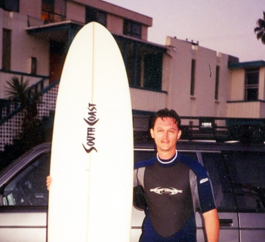 Fleming poses on a surfing expedition. He had many different jobs before teaching.