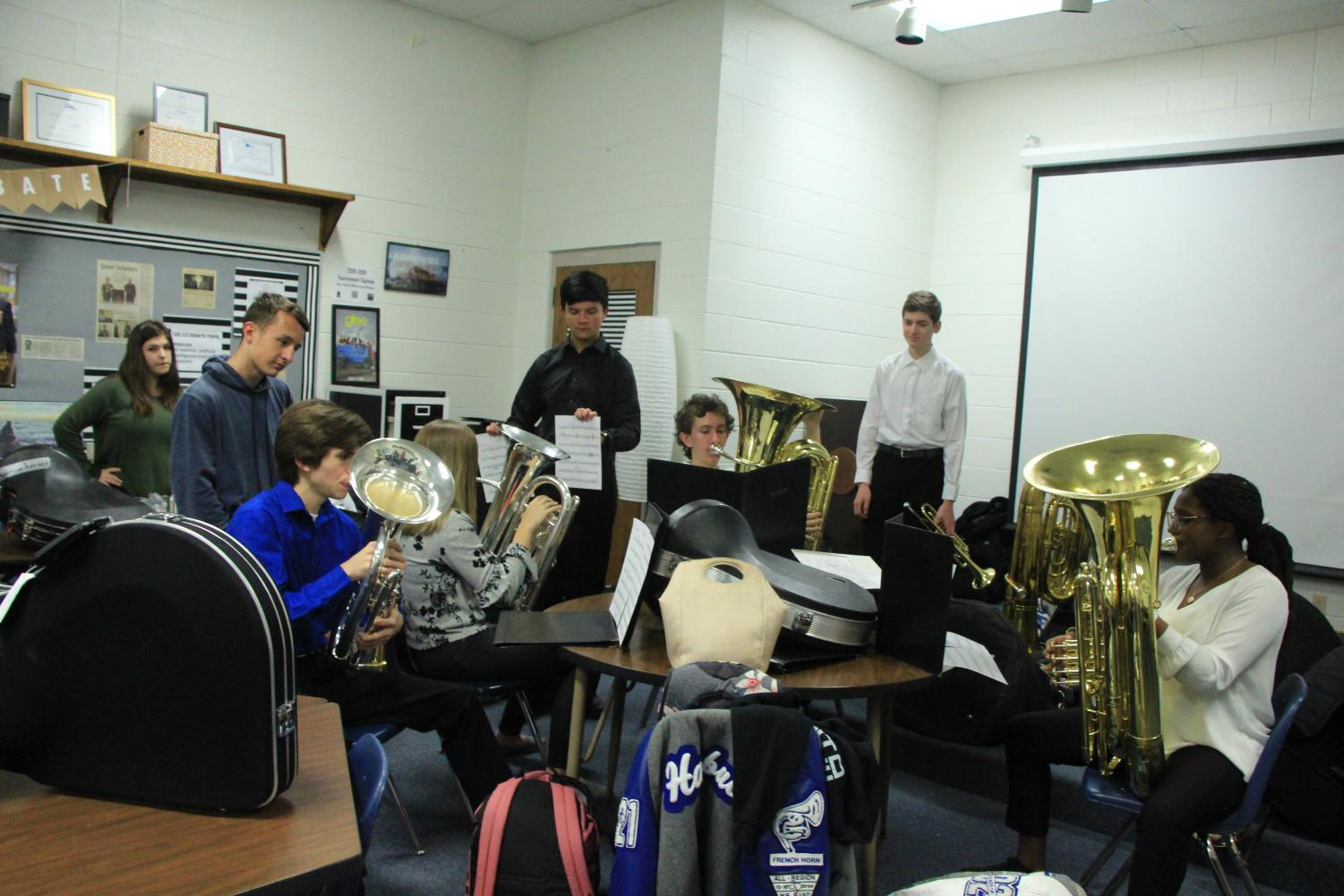 Band students warm up and practice in the debate room. They were able to run their music before they performed.
