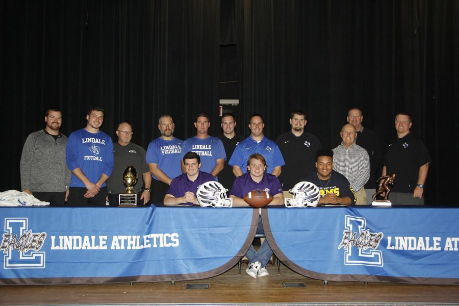 Senior football athletes James Sandifer, Dillon Heinaman and Cason Cheney pose with their coaches at the signing ceremony. Heinaman and Sandifer will be attending Hardin-Simmons University in Abilene, while Cheney will be going to Texas Wesleyan University in Fort Worth.