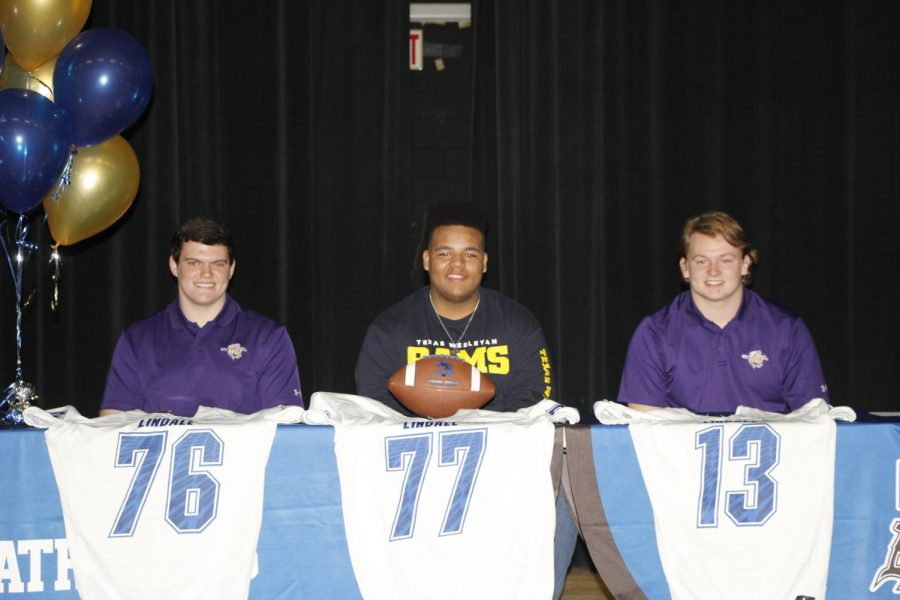 The football players sit at the table awaiting the moment when they will finally sign to play college football.
