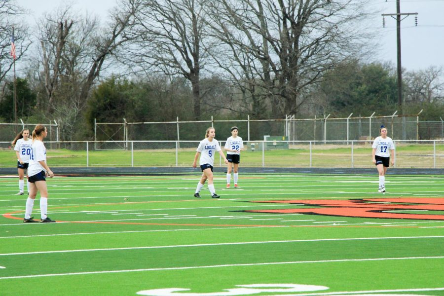 The players rush across the field to continue the play. They won against Grand Saline 8-0.