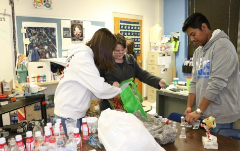 Art one students in Harrison's class sort through plastic products. Their focus is ocean conservation, and the sculpture will be  displayed in the hallway outside of Harrison's classroom.