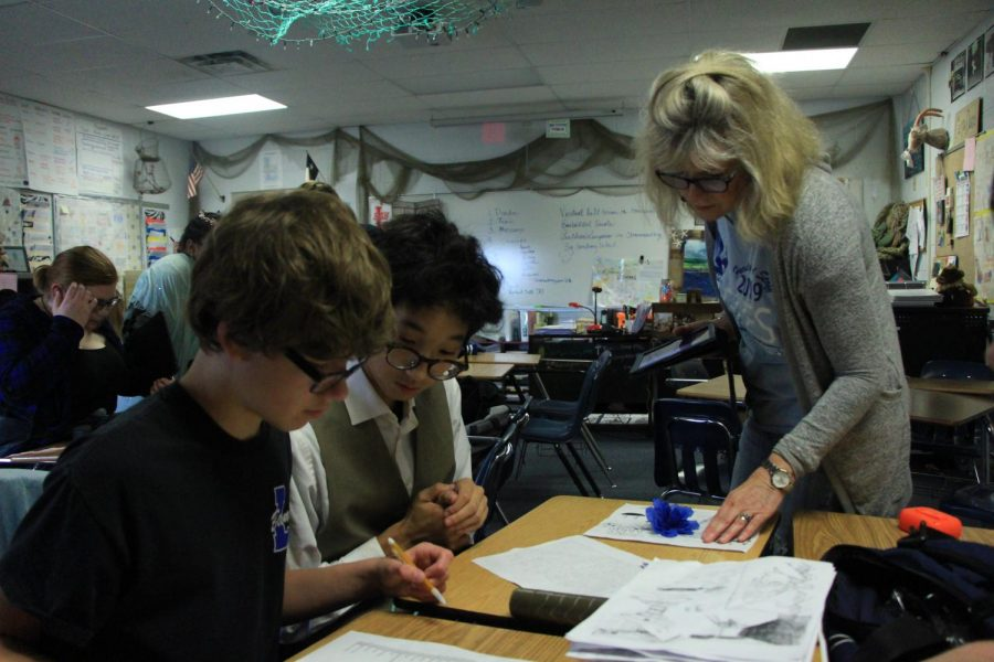 Snow help her students work on a porject. They will  present their characters and scenes during the wax museum activity.
