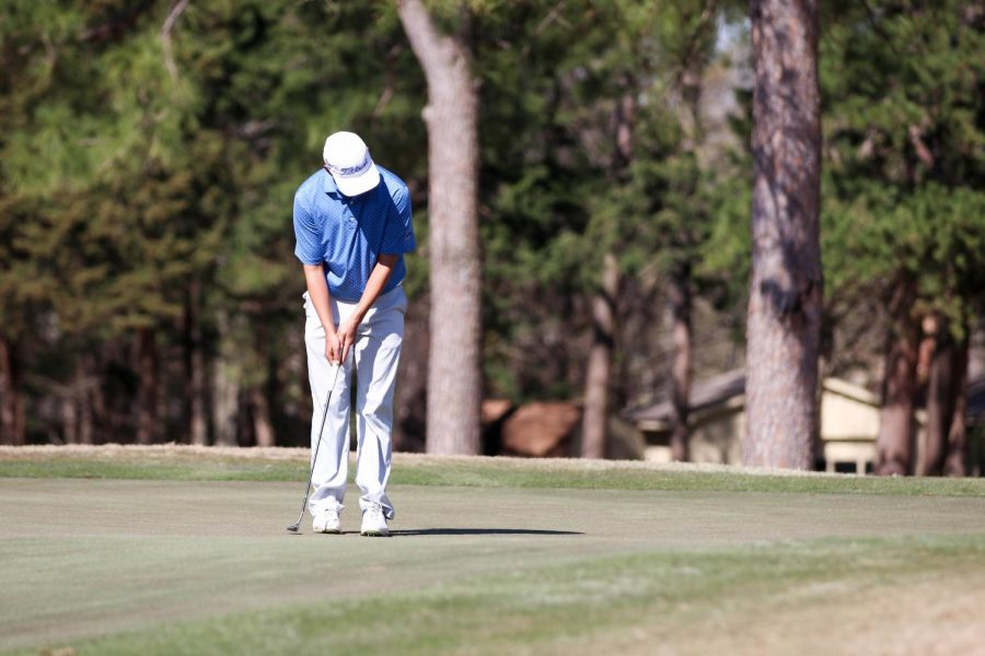 Senior Ryan Esparza prepares to putt the golf ball. The golf tournament was held at the Hideaway golf course.