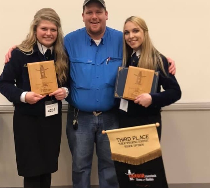 Seniors Ashlyn Ellgass and Isabella Yoder stand at awards with coordinator Stephen Hindman. Both of them placed in the prepared speaking category of the contest.