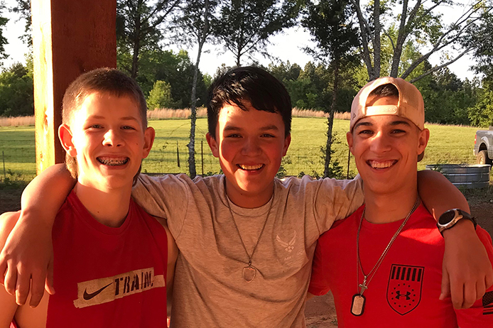 Evan Marquez (middle) poses with two of his friends.