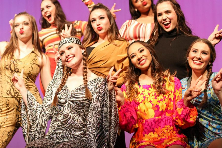 Seniors Maryann Castaneda and Kayley Kraig along with junior Autumn Brown along with other drill team members hold up peace signs to end their dance routine. They performed in attire from the 1960s-1970s era.