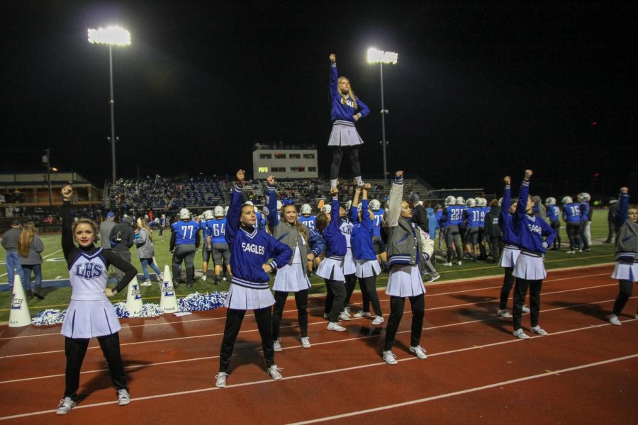 The varsity cheerleaders do  stunt on the sidelines at the Jacksonville game. The cheerleader will attend a cheer camp this summer and paint signs for the school year.
