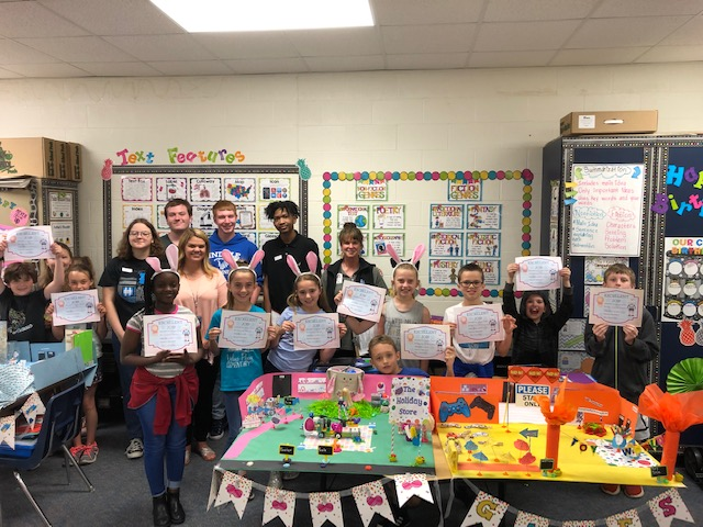 3rd grade students pose with their awards and high school mentors. Each team received an award based on creativity, programming difficulty and unique ideas.