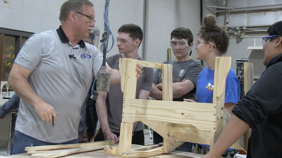 Coach John Phillips gives guidance to his students to help them build their chair. He started building them 14 years ago.