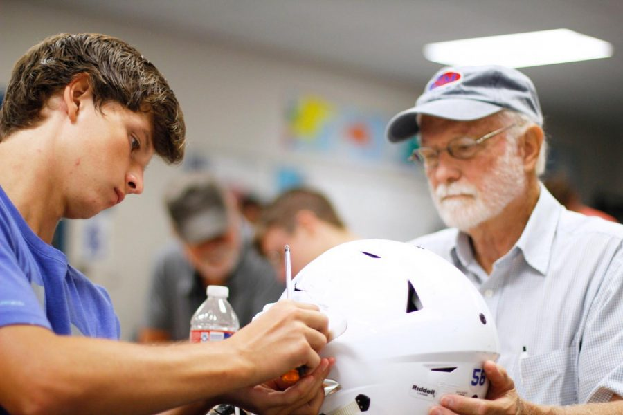 Senior+Copeland+Taylor+and+his+grandfather+place+the+%22EAGLES%22+decal+on+his+helmet.+This+event+was+started+last+year+as+a+way+to+strengthen+bonds+with+the+community.
