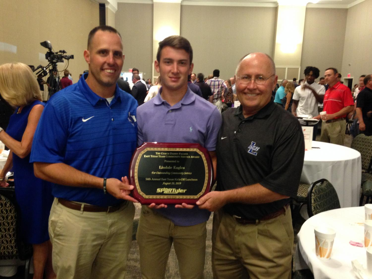 Coach Cochran, senior Conner Boyette, and AD Mike Maddox accept the community service award on behalf of the football team.