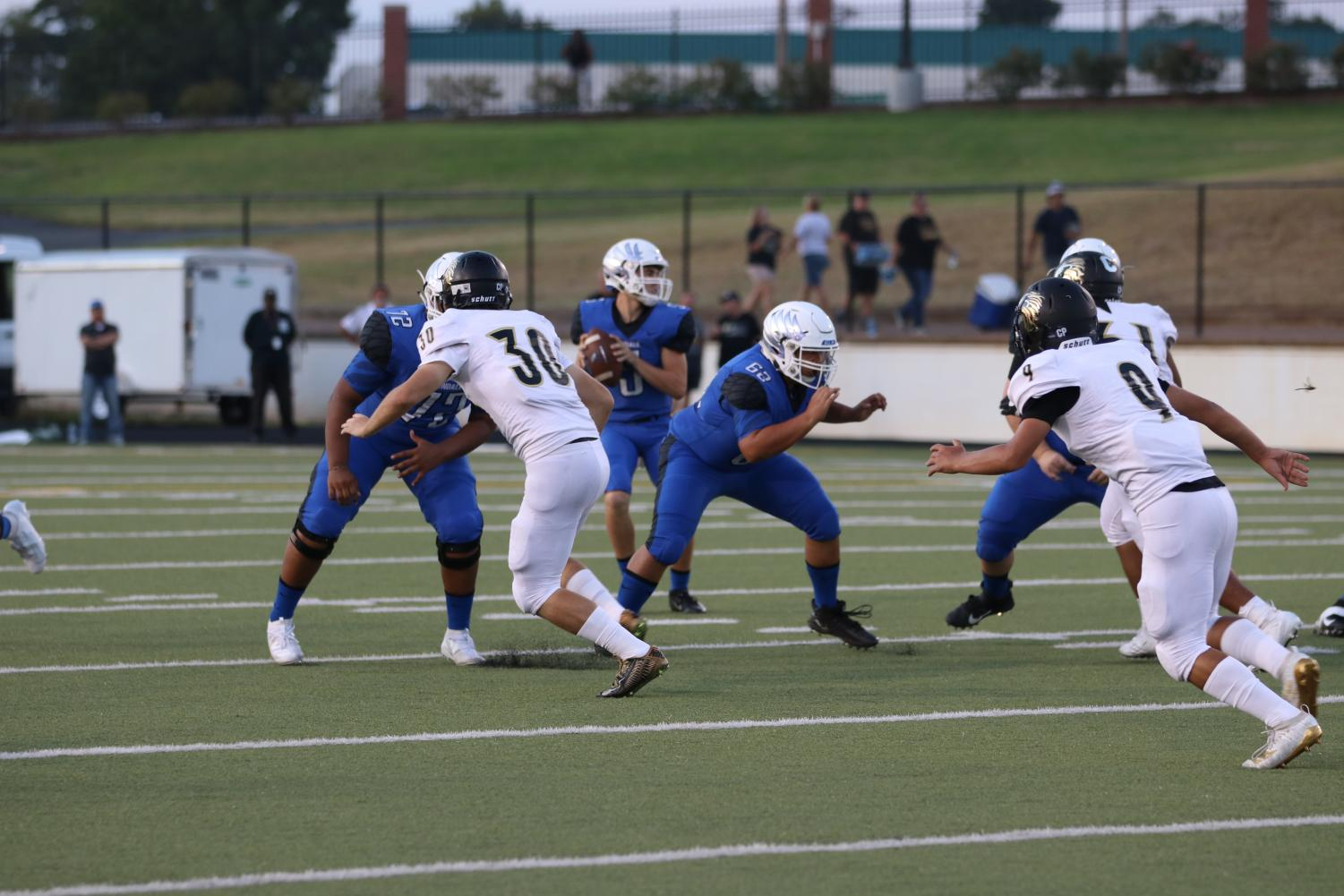 Senior quarterback Brayson Campbell sits in the pocket, waiting for a chance to make a good throw while his teammates block the Kaufman opponents for him. The Eagles won the game 45-10.