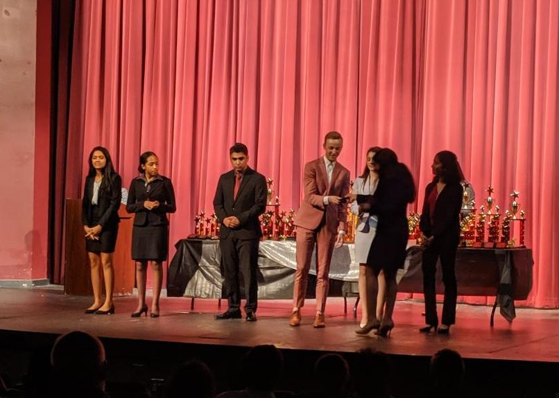 Senior Jeremy Guidotti receives his fifth place trophy. Guidotti competed in Prose interpretation at the tournament.