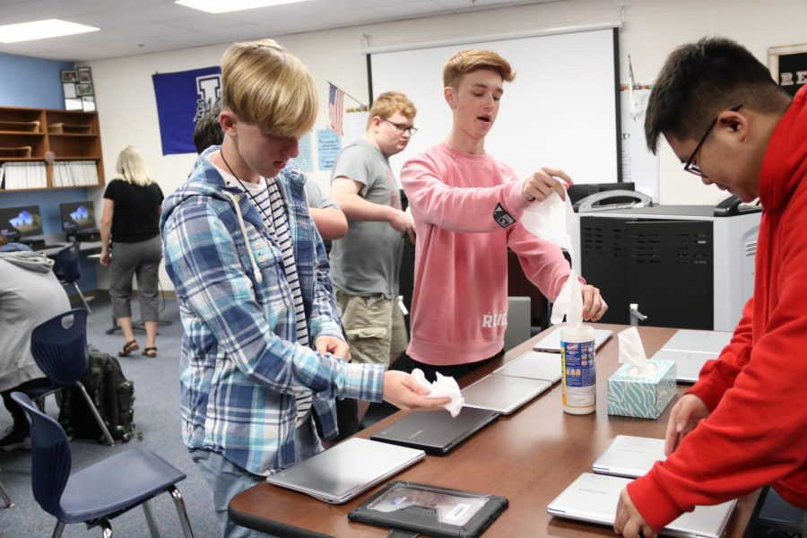 Juniors Blake Williams, Brooks Broughton and Suldee Narangerel clean Chromebooks from the cart. This was during their 5th period computer maintenance class.