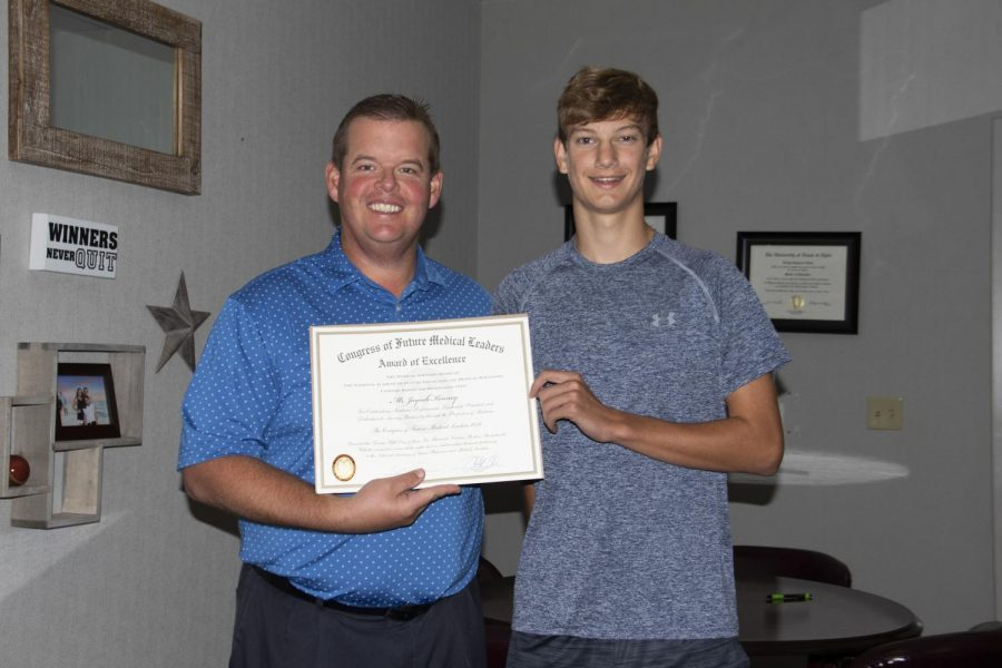 Junior Jaycob Kenney receives an award for his attendance at the Congress of Future Medical Leaders. Kenney was chosen to represent the State of Texas at the national congress