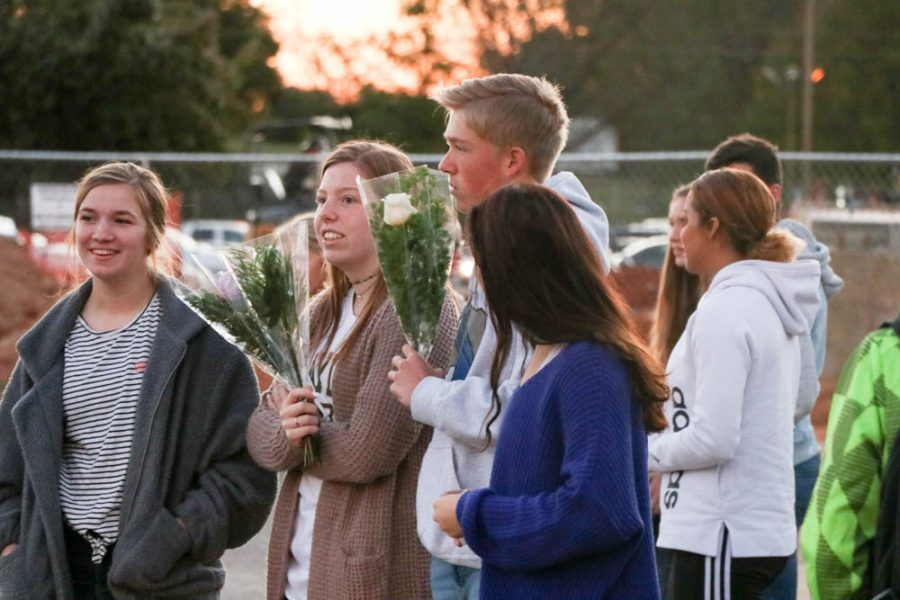 Floral design students wait in the student parking lot to pass out roses. Over 100 roses were passed out.
