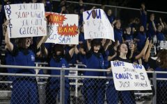 Band Members Make Signs for Football Players