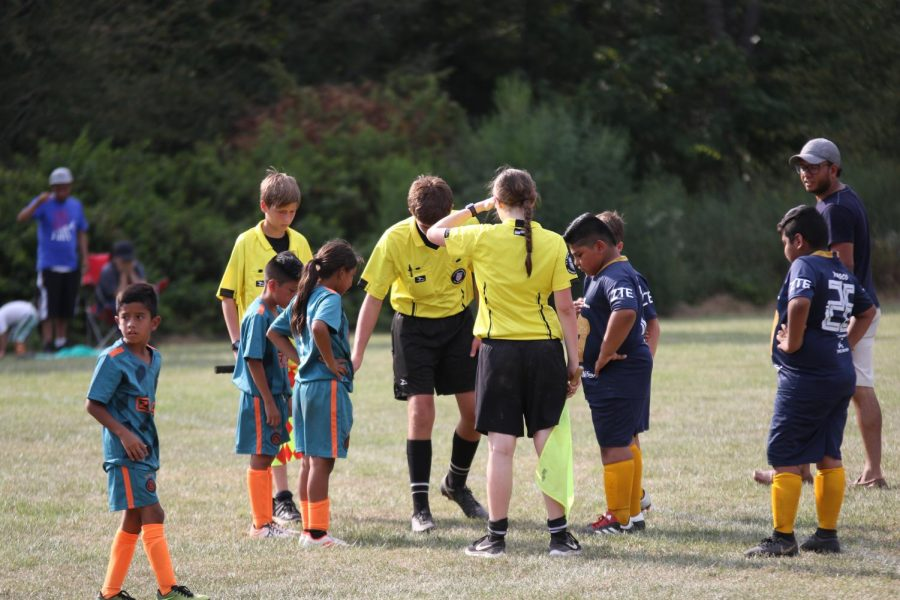 Senior Colleen Starkey, eighth grader Otto Straus and seventh grader Seth Derksen perform a coin toss at a tournament game. Many referees for youth games like this have quit due to unruly parents or coaches.