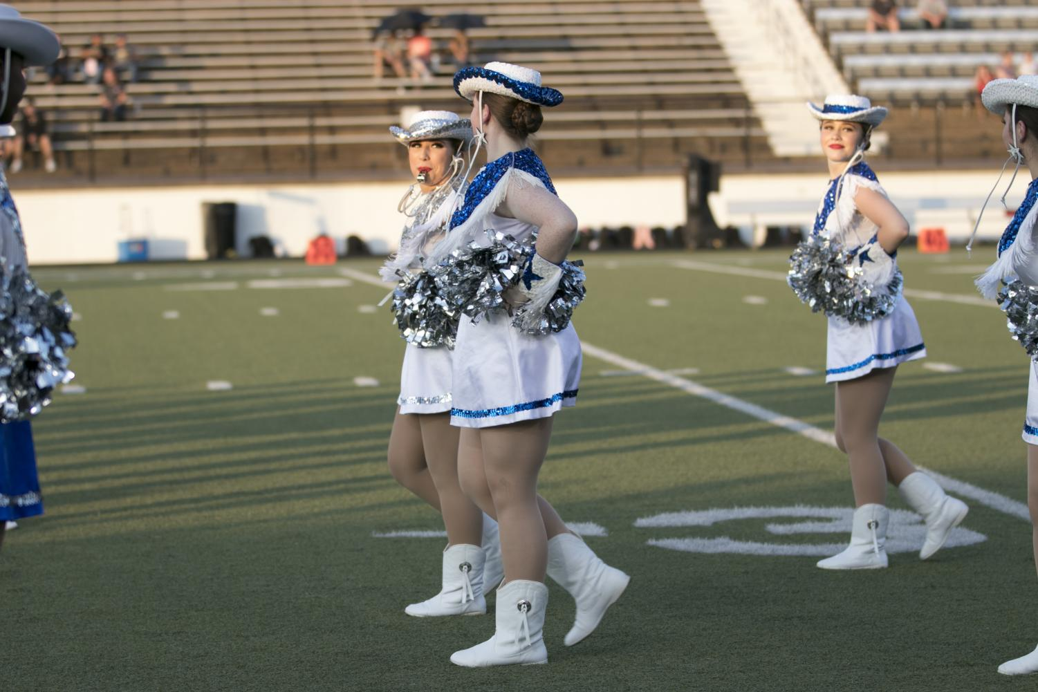 Senior Syndi Segroves walks onto the field with her fellow Drill Team officers at the beginning of varsity football game against Kaufman.