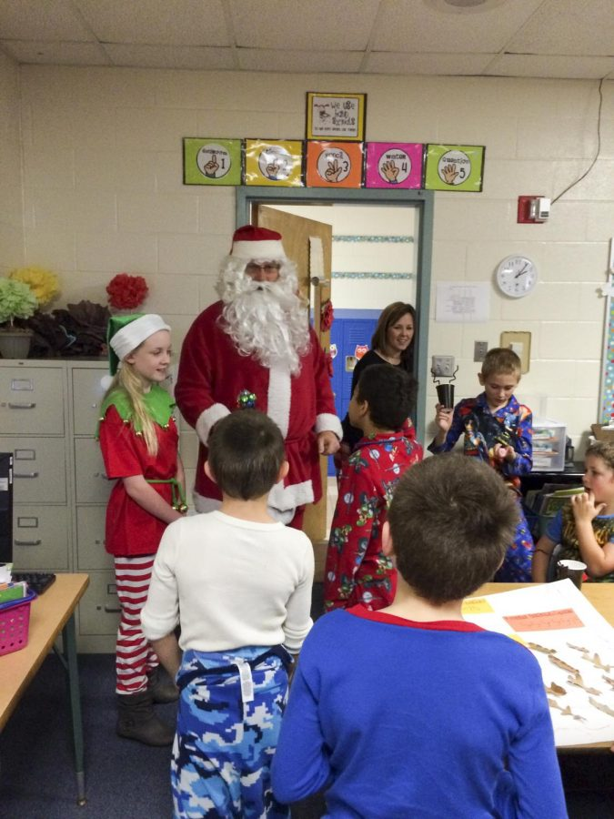 Coach John Phillips dressed up as Santa visits College Street Elementary. He visited different classrooms to spread the Christmas spirit.