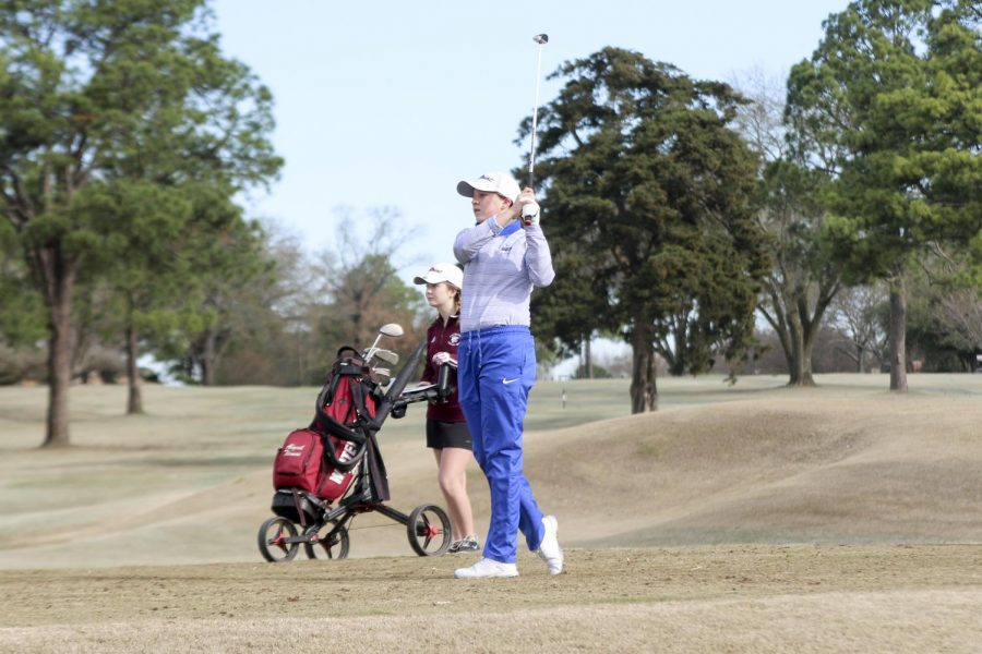 Freshman Julee King swings her club and watches the ball. This was her fourth tournament she competed in.