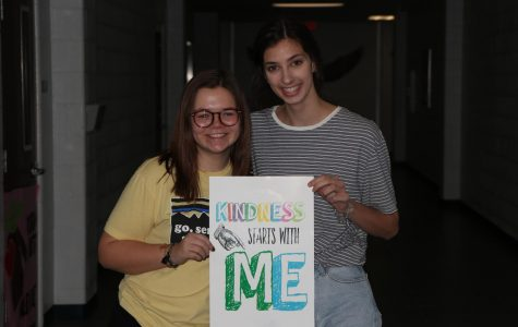 Juniors Abigail Powell (left) and Abby Payne (right) hold the Kindness Challenge sign. It was a week-long challenge that spread positivity around the school.