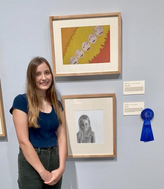 Junior Carlin Root poses next to her a graphite portrait of a young lady named Evy. Root won the the Tyler Museum of Art Annual Senior Exhibition as a junior