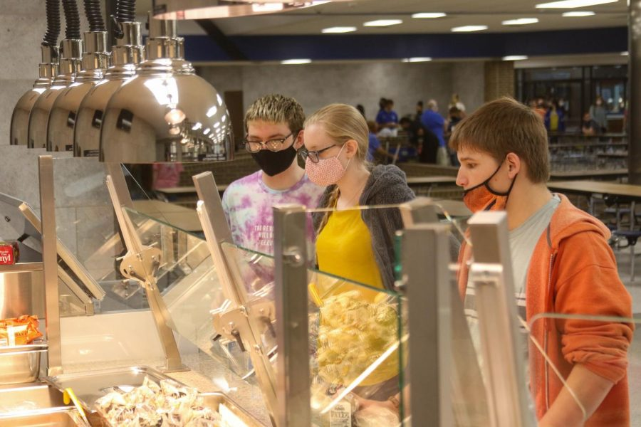 Students wait in line for lunch in the cafeteria. The cost for a lunch is normally $5.