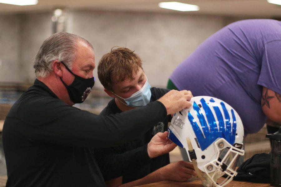 Senior Jaret Allen sticks his Decal on his helmet.