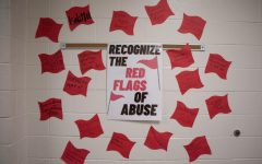 "The ""red flags"" on the wall outside of Ridge's classroom. ""Most young adults do not believe they are being abused until they are out of the relationship and home,"" junior Andie Lewis said, ""Really, abuse is not being able to go out because the abuser would get mad or even hurt themselves to keep you close."""