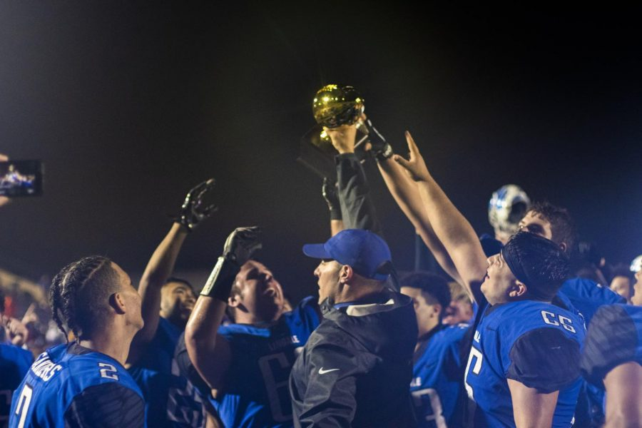 Head coach Chris Cochran holds the golden football trophy with the team. The Eagles won against Austin LBJ in the semifinal game with a score of 31-28.