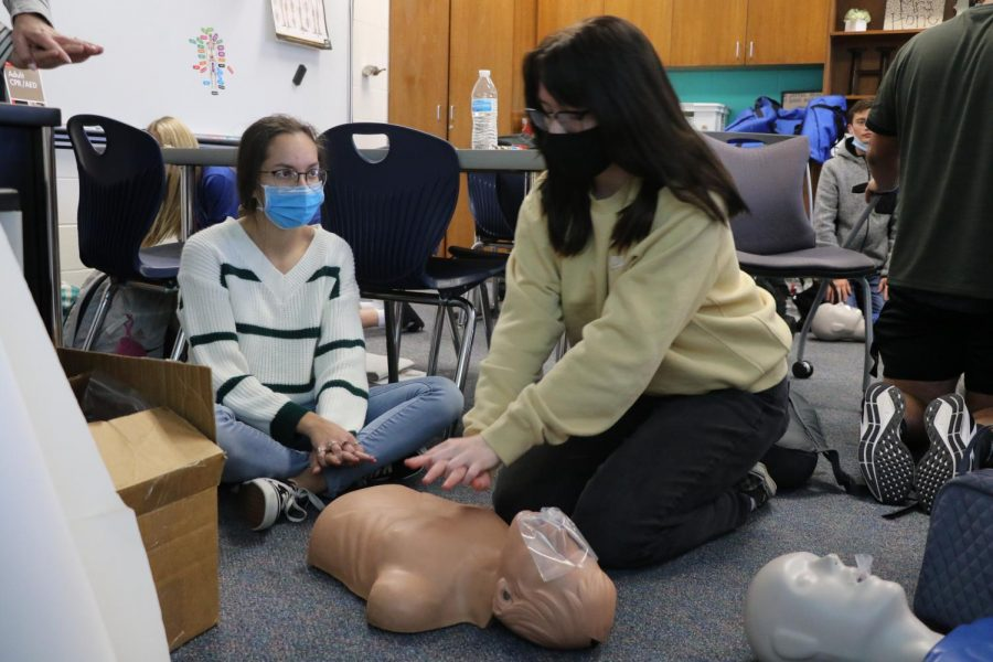 Sophomore Kylie Hester practices CPR on the CPR dummy.
