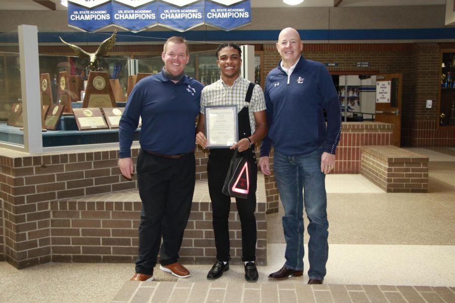 Senior Kevin Willis holds his award with prinicpal Jeremy Chilek and State Farm member RJ Collins. The award is for his efforts in maintaining the Lindale attributes.