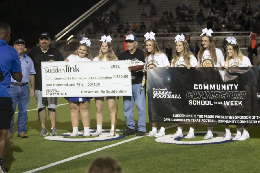Community leader Larry Wilson poses with the cheerleaders as he accepts his award. Wilson received his award after first quarter during the football game on Sept. 17.