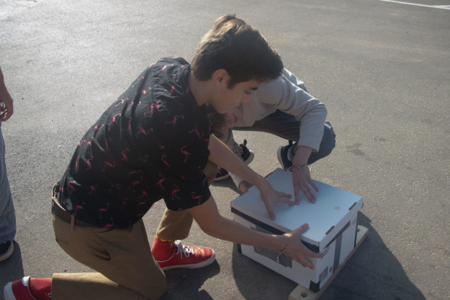 Seniors+Tyler+Chamberlain+and+Chris+Tate+prepare+their+camera+to+take+a+picture+in+the+parking+lot.+The+camera+was+made+from+cardboard+and+tape.+Photo+by%3A+Jaida+Jones