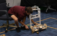 Freshman Isaiah Yard removes the weights from the robot to test the wheels.
